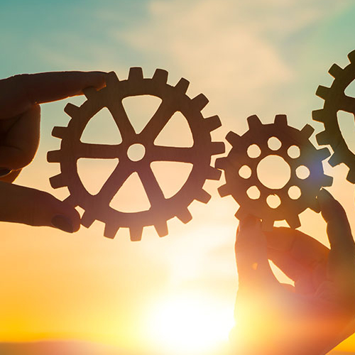 Hands holding up gear cogs up with the sun in the background