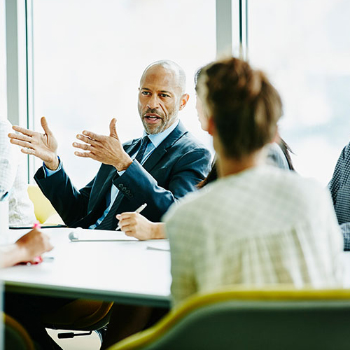 Man gesturing in a meeting with a woman and another man