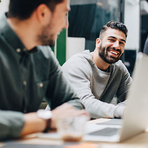Man smiling at another man who is on his laptop