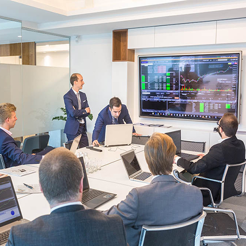 Screen with graphs on it in a boardroom with multiple people