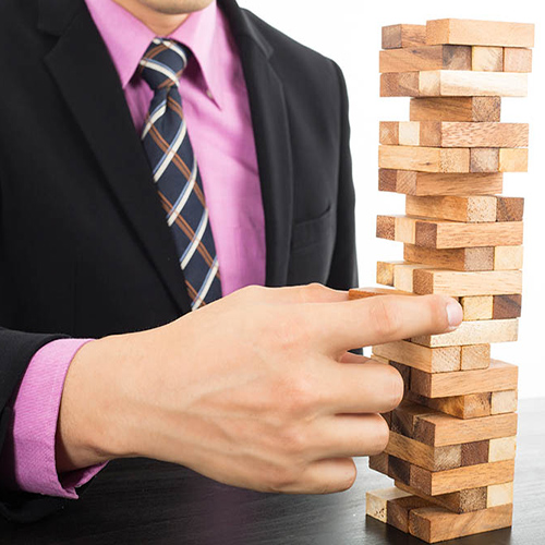 Man in pink shirt, tie and suit putting a jenga block into a tower