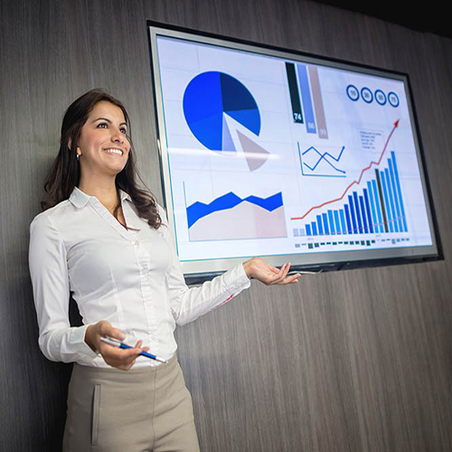Woman in white shirt presenting in front of a screen with a graph