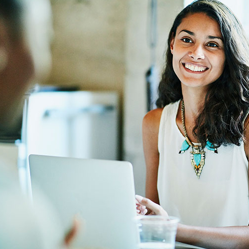 Woman sitting with laptop and smiling